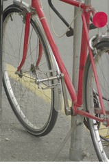 A red bicycle is locked to a gray pole, sitting on an asphalt sidewalk.