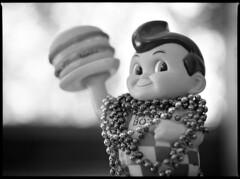 Meaty Boy Rising (Voxphoto) Tags: blackandwhite bw bokeh burger experiment delta100 quiff bigboy shallowdof mardigrasbeads mamiyam645 1closeuplens mamiyasekorc11028