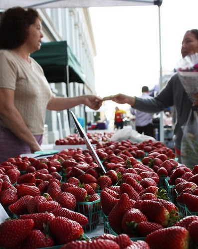 A woman makes a purchase at her local farmers market. A single farmers market purchase can have a big impact on the local economy.  (Photo courtesy of Real Time Farms)A woman makes a purchase at her local farmers market. A single farmers market purchase can have a big impact on the local economy.  (Photo courtesy of Real Time Farms)