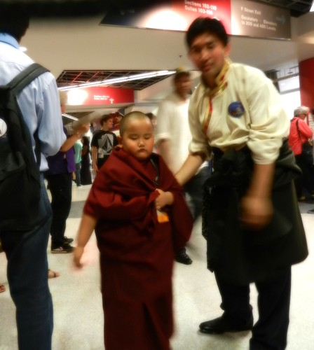 Young Taksham Tulku, & Sonam Sangpo, of Ugyen Mindroling Monastery, Clement Town, India, pauses to be photographed with a bright red ball of light energy apparently in his right hand, conclusion of Kalachakra for World Peace, Verizon Center, Washington DC by Wonderlane