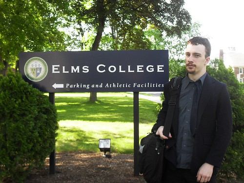 Photo of Jacob in front of Elms signage