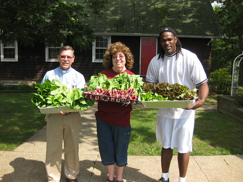Chaplin Wally Merner, manager of LICC Emergency Food Center, Ann McPartlin from The Garden at St. Mark's, Gregory Lucas, food pantry worker, showcase freshly harvested produce.