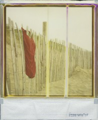 Red Bathing Suit (Lizzie Staley) Tags: red summer england green film beach fashion yellow vintage fence polaroid sx70 seaside sand dunes retro 1940s devon 600 damaged expired swimsuit bathingsuit woolacombe 40s 2011 borderless roidweek2011