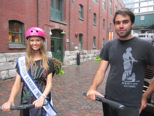 Miss Teen Canada, lauren Howe with Jason from Segway Ontario beside the wreck of the old truck on Case Goods Lane of the historic distillery district.