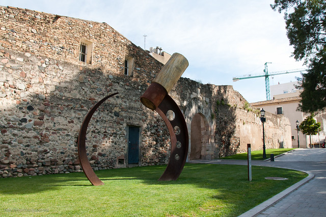 Estela de Falç: Un monumento frente a los restos de la muralla y una de sus puertas