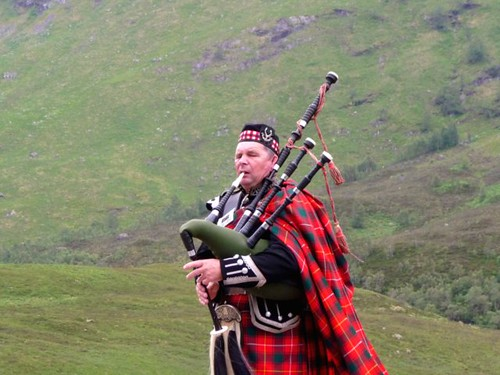 Bagpiper in the  Scottish Highlands by Ginas Pics