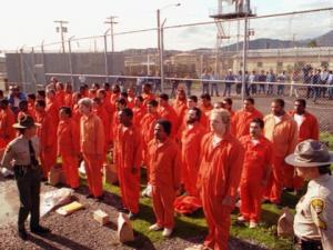 prisoners wearing orange jumpsuits stand at attention at in the san quentin prison yard