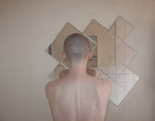 Person with shaved head looking at a mirror with their back to the camera.