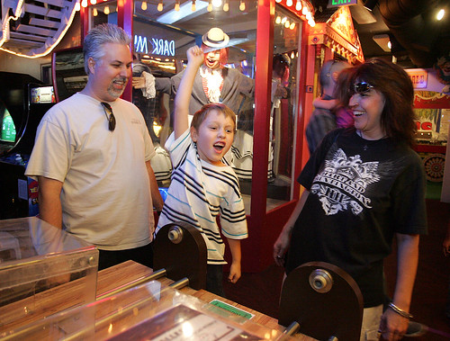 Parents Scott and Amy Craig of Sacramento watch son Ian Craig, 7, reacts to winning on the Bowler Roller game.