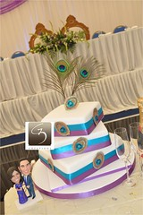 Peacock twist wedding cake (G3 Creations (Nikis Cakes)) Tags: blue wedding london cake square purple weddingcake feather twist peacock middlesex edgware creations fondant gumpaste 3tier eggless sugarpaste peacockwedding peacocktheme peacockweddingcake g3creations wwwg3creationscom g3wedding egglesspeacockweddingcake