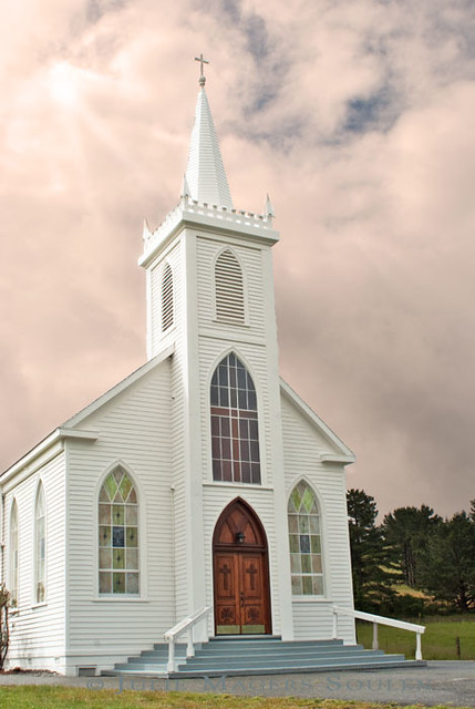 An architectural photo of a white clapboard Christian church with rays  of light shining down from a cloud filled sky.