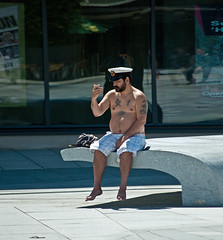 """Damn but I'm looking fine!"" (The Image Den) Tags: candid southampton hampshire guildhallsquare sunnyday shorts moobs fat obese body tats tattoos cap sailor flabby sitting alone checkinghimself mirror solitary nikon d5000 geo:lat=50907832 geo:lon=1405103 geotagged"