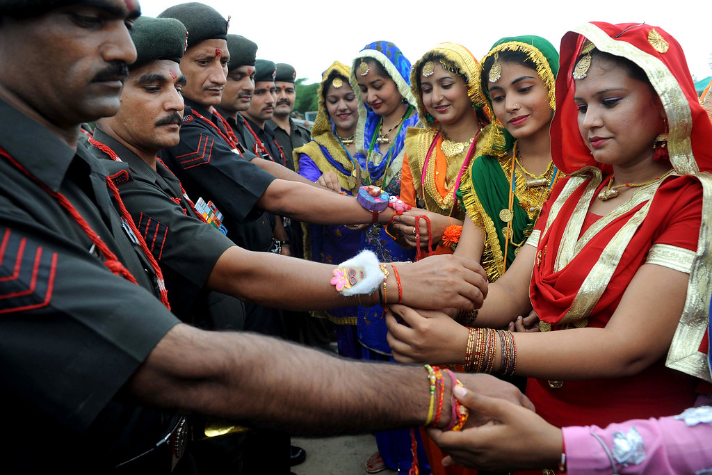 Tying rakhi onto soldiers' wrists