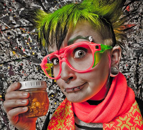 Girl with glasses and green hair holds jar of mysterious yellow liquid
