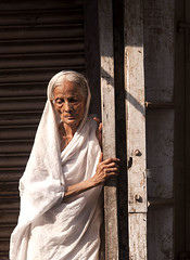 Old Lady (Shubh M Singh) Tags: road old light red sea portrait people woman india white yellow architecture hope evening twilight hands nikon alone peace dusk walk east thoughts cotton shore simplicity future d200 thin minimalism nikkor grip widow solitary gaze sari orissa gnarled puri downcast cuttack nikonstunninggallery