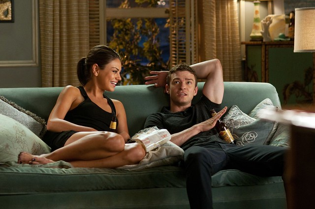 Mila Kunis, a young white woman, and Justin Timberlake, a young white man, sitting on a green couch talking and drinking beer out of bottles in the movie Friends with Benefits