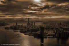 In the East Lies a City (TIA International Photography) Tags: china city summer sky urban mountain building history water sepia skyscraper tia real hongkong hotel bay harbor boat asia ship commerce cityscape dragon estate waterfront harbour south centre horizon hill overcast august vessel center victoria aerial east international empire promenade housing marco hyatt metropolis sheraton elevation  kowloon peninsula legend icc polo tsimshatsui height myth dynasty intercontinental 2010 harbourcity starhouse visipix tosinarasi tiascapes tiainternationalphotography