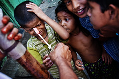 tooth ache (...Photography by Focus...) Tags: street travel boy portrait woman india man girl kids youth children essay asia raw colours candy district muslim capital young documentary commercial bombay sweets reality editorial vendor maharashtra lollipop mumbai recycling hindu tamil slum dharavi slumdog