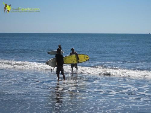 Three guys surfing in a costa rica beach