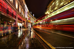 Walking Down Regent Street (TIA International Photography) Tags: street uk light england urban motion blur reflection building bus london wet rain fashion june shop retail architecture night tia shopping landscape jack concrete lights spring slick neon traffic zoom britain circus pavement flag united union great trails picadilly kingdom pedestrian stop rainy transportation streams curve sleek regents curtis tosin curvature hawes arasi tiascapes tiainternationalphotography