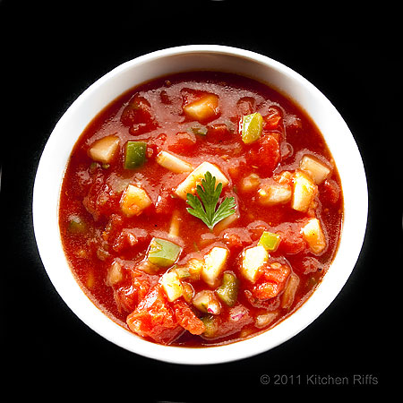 Gazpacho in white bowl on black background, overhead view