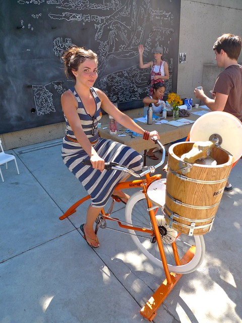 woman pedals a bike that stirs ice cream