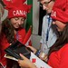 Canadian team members examine an iPad application developed by another exhibitor.