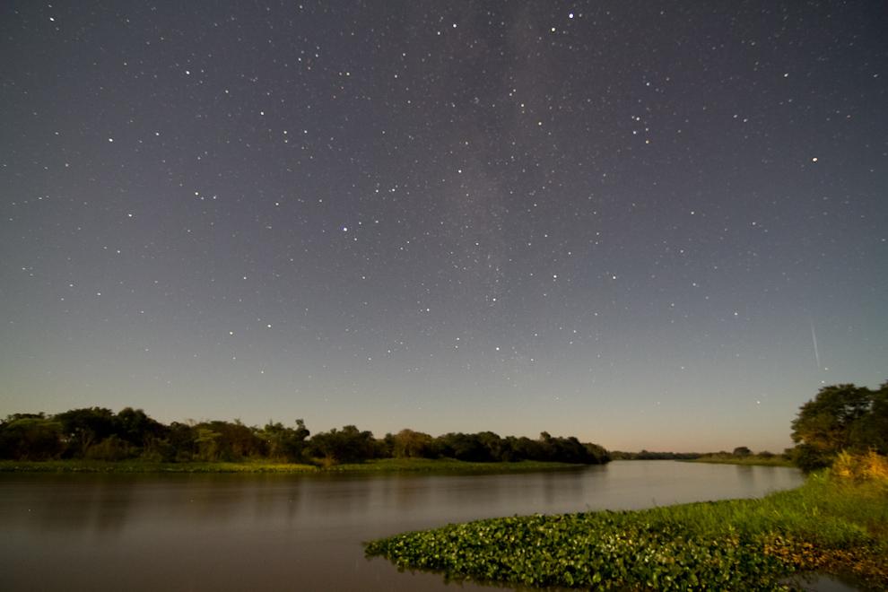 Una toma de larga exposición muestra parte de la Vía Láctea en una fría noche a orillas del Río Jejuí, una estrella fugaz se observa en el costado inferior derecho en  Puerto La Niña, San Pedro. (Tetsu Espósito)