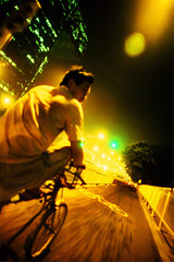 Pedicab (Jonathan Kos-Read) Tags: china road street city green bike yellow night asia crossprocess tricycle chinese beijing fast wideangle motionblur remkoolhaas lensflare lonely    pedicab guomao trishaw goldenratio   chinesestreet cctvtower   migrantworker  sigma20mmf18exdg  beijingstreet chinesetv 20mmf18exdg  nikond700