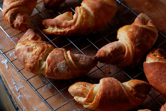 Home-made croissants cooling on a baking rack