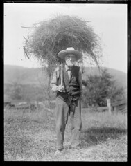 Old farmer with pitch fork full of hay
