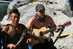 One of the guides supplying some music for the locals on the Kameng river Adventure rafting and Kayaking trip