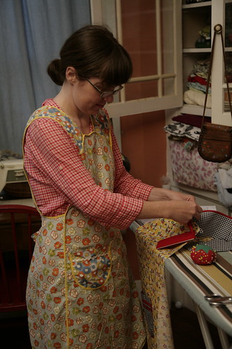Sewing an apron, in an apron.