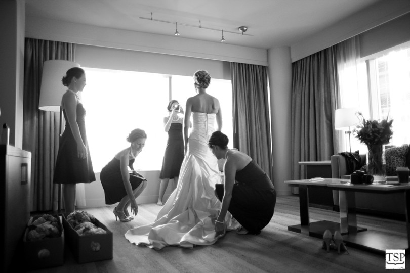 Bride with Bridesmaids Straightening Dress