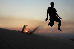Fly me to the moon... (WeeLittlePiggy) Tags: sunset sun beach night jump sand northcarolina outerbanks leap jockeysridge