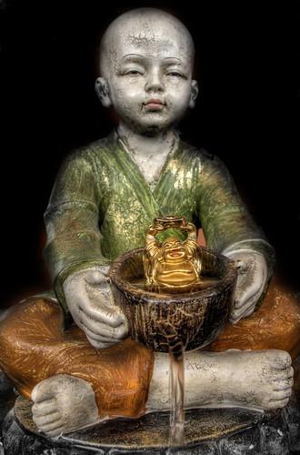 Buda tomando un baño en una fuente de plástico