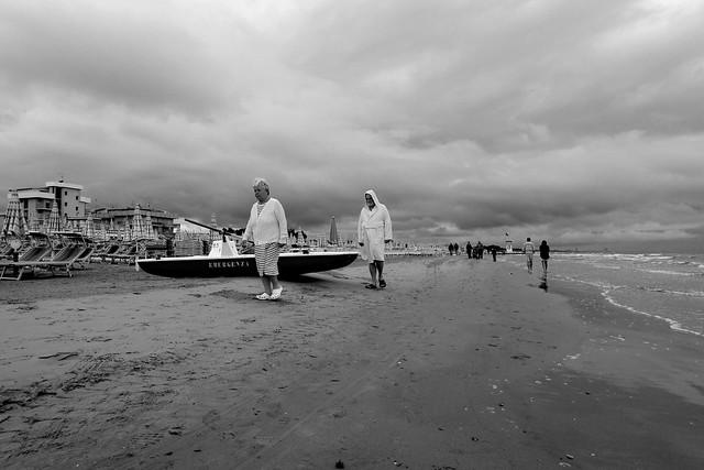 La couple sur la sable et l'homme avec le peignoir de bain