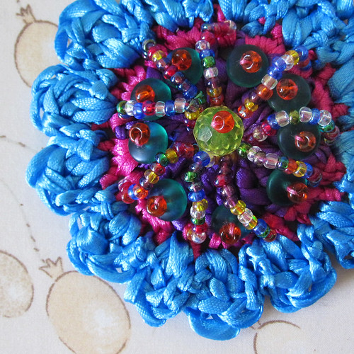 Crochet flower with embroidered accents