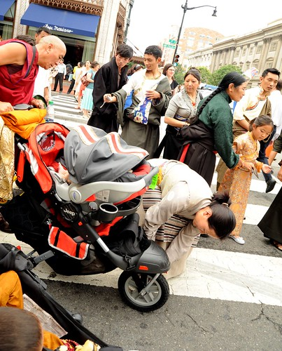 Tibetan families, monk, lady fixing baby stroller, men, women and girl wearing chubas, taking a photo,Happy Birthday to His Holiness the Dalai Lama Parade, Kalachakra for World Peace, Washington D.C., USA by Wonderlane
