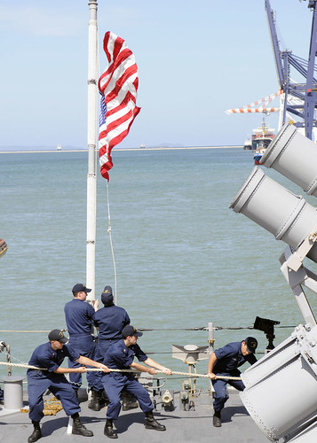 Sailors hoist ship colors during special sea and anchor detail aboard USS Cowpens (CG 63) as the ship is moored in Laem Chabang