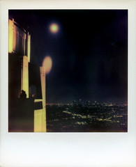 Smooching In The Shadows Under The Double Moon (tobysx70) Tags: california park ca city toby summer moon color night project out polaroid sx70 lights la los kissing couple downtown cityscape shadows skyscrapers angeles under july double observatory tip shade hollywood week push hancock griffithobservatory griffith 70 making highrises impossible smooching roid the in px 2011 roidweek theimpossibleproject px70colorshadepush tobyhancock impossaroid