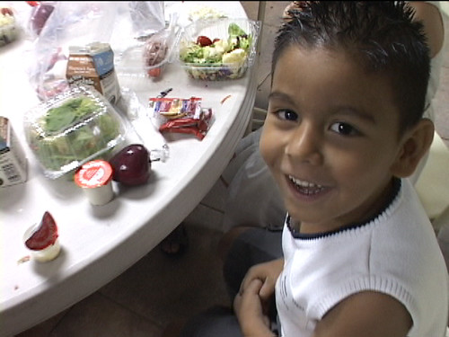A young SNAP recipient eats at the Help 4 Kidz Café while his parents apply for SNAP with the help of a volunteer case manager.