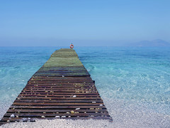 Into a Turquoise Infinity (kenny barker) Tags: sea mountains color water turkey coast lifebelt turquoise jetty pebbles panasonic shore g1 oludeniz hypothetical waterenvirons pinnaclephotography