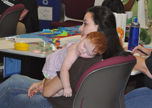 A local WIC staff member holds her sleeping baby as she listens to the peer counseling instructor.