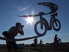 Flying bike - Tempelhof Airport - Berlin (Lumatic) Tags: life blue summer portrait sky people sculpture sun berlin history sunshine bicycle silhouette start germany deutschland cycling cyclists airport wings energy photographer cyclist symbol silhouettes clear flare shooting flughafen sonne takeoff airfield tempelhof cycler gettygermanyq4