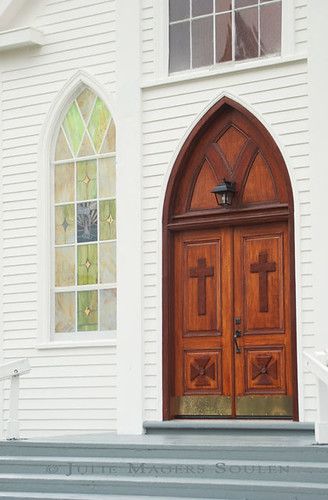 An architectural photo of a beautiful wooden Christian church door.