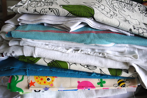 A stack of fabric and tee shirts to be upcycled into burp cloths