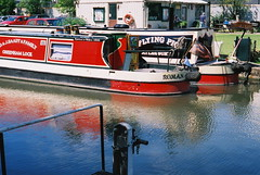 Narrowboats in Aylesbury Basin (cycle.nut66) Tags: blue red sunlight green film water grass canon boats 50mm canal fuji arm 14 union grand scan 200 a1 aylesbury stern tiller rudder fd narow narrowboats