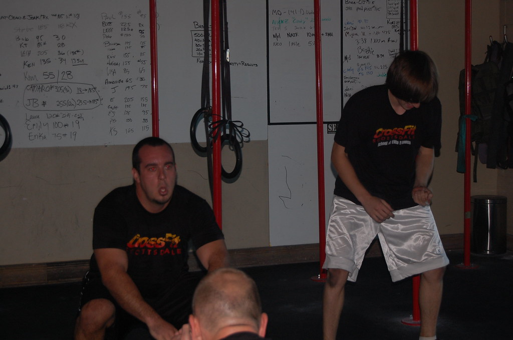 Chris holds his squat while Geofff Jams on the Air Guitar during sealfit at crossfit Scottsdale