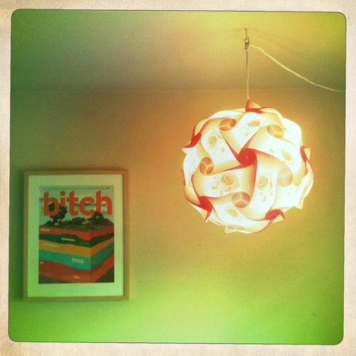 the Old cover print hanging on a wall with a pink glowing lantern next to it. the photo is green-tinged